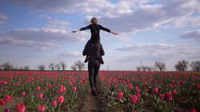 Children-parents relationship, daddy with adolescent boy spread arms to side sitting on shoulders having fun on blossom. Field of tulips against sky stock video footage