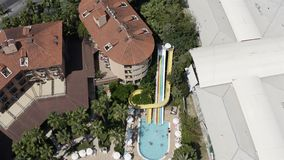 Children with parents ride a water slide diving into the pool. Top shot