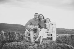 Children and parents sit on bench on hay. Girls, women and men smile on natural landscape. Mothers and fathers day. Happy childhood, family, love. Summer Stock Images