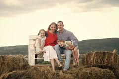 Children and parents sit on bench on hay. Girls, women and men smile on natural landscape. Mothers and fathers day. Happy childhood, family, love. Summer Stock Photos