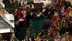 Children and parents wait in line at Coquitlam Center Mall to visit and have their picture taken with Santa Claus. stock video footage