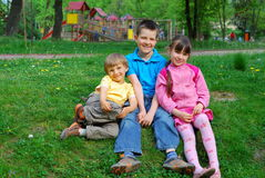 Children in park. Three young children seated on the grass in a park with a playground in the background stock photography