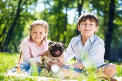 Children in park with pet. Adorable boy and girl in summer park with their dog Royalty Free Stock Photography