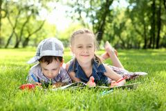 Children in the park reading a book Royalty Free Stock Photo