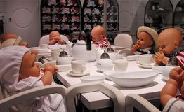 Children party. Funny arrangement with babies dolls at an elegant table royalty free stock photo