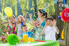 Children with party hats. And trumpets during garden party Stock Image