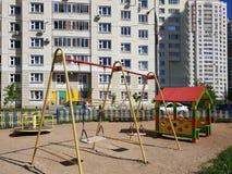 children& x27; patio de s con los oscilaciones en patio del edificio residencial en la ciudad, Rusia Fotos de archivo libres de regalías