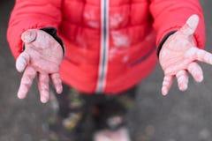 children& pequeno x27; braços de mãos sujos de s estendidos à parte superior no fundo do asfalto imagens de stock