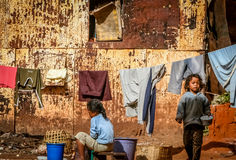 Children perform daily chores. Two little girls outside their shack performing daily chores like washing dishes and doing laundry stock photo