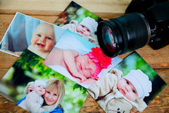 Children is photos and camera on a wooden background. Royalty Free Stock Photos