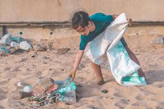 Children picking up Plastic bottle and gabbage that they found on the beach for enviromental clean up concept royalty free stock images