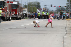 Children pickup candy in a  parade in small town America Royalty Free Stock Photos