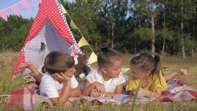 Children on picnic read book, cute kids enjoy reading interesting stories while relaxing in woods on summer weekend