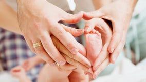 Children&#39 ; pieds de s dans des mains de mère et Photo stock