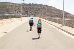 Children in piggyback race. Walking down an emty road Stock Image