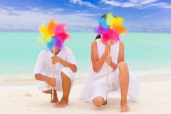 Children with pinwheels. Two children playing with colorful pinwheels on a tropical beach Stock Photo