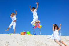 Children and pinwheels on sand. Three children leaping and playing with colorful pinwheels and buckets on a white sandy beach with a blue sky in the background Royalty Free Stock Photo