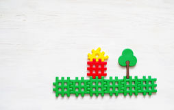Children plastic blocs on a white wooden surface. Children`s background. Colorful toys for kids. Conceptual image of the house, family, nature stock image