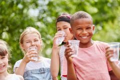 Children with plastic cups drinking water. In summer in the park Stock Photography