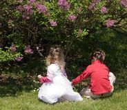 Children at Play. Boy and girl playing under a bush of purple spring lilacs Stock Image