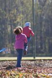 Children At Play. Little girl pushing her little sister on swing at local park Stock Photography