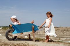 Children at play. Little girl pushing her sister in a wheelbarrow Royalty Free Stock Photos