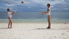 Children play with a ball on the beach outdoors. Two young girls playing with a sword on a tropical beach on a background of blue sea stock video footage