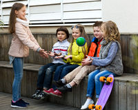 Children play with a ball. Beautiful group of children sitting on bench and playing with ball and smiling Royalty Free Stock Photo