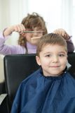 Children play in the barbershop Stock Photos