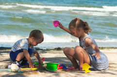 Children play on beach. Small girl and boy play with sand near sea Stock Photography