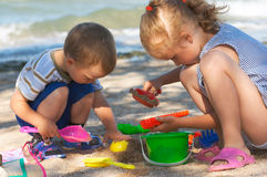 Children play on beach. Small girl and boy play with sand near sea Royalty Free Stock Photography