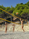Children play beach volleyball. Three girls - best friends playing volleyball on a sandy beach near the pine trees along a sunny day. Vertical color photo Royalty Free Stock Photos