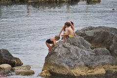 Children play on the big stones. Herceg Novi, Montenegro – June 23, 2016: Scene with children play on the big stones at the coast Stock Photo