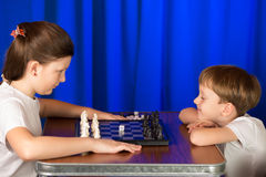 Children play a board game called chess. Royalty Free Stock Photography