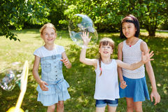 Children play catching soap bubbles Stock Images