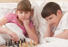 Children play chess in a bed Stock Photo