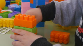 Children play in color cubes. Close-up construction of children`s designer