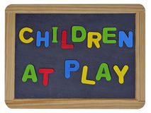 Children at play in colored letters on slate Stock Photos