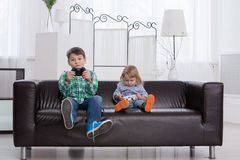 Children play in the console home. Brother and sister playing in the top box on a couch in a bright room Stock Photos