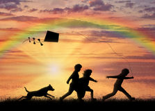Children play with dog and kite sunset Stock Image