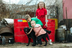 Children play at dump with dog Stock Photo