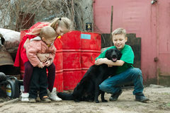 Children play at dump with dog Royalty Free Stock Photos