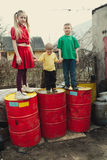 Children play at dump drums Stock Photography