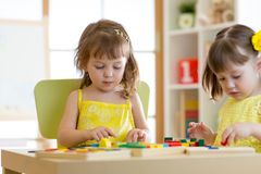 Children play educational toys in kindergarten royalty free stock photo