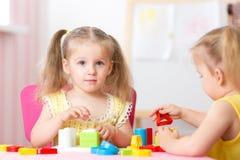 Children play educational toys in preschool stock image