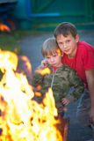 Children play with fire in the grill Stock Photo