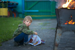 Children play with fire in the grill Royalty Free Stock Images