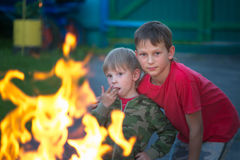 Children play with fire in the grill.  Stock Image