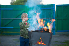 Children play with fire in the grill Royalty Free Stock Image