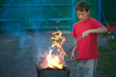 Children play with fire in the grill Stock Images